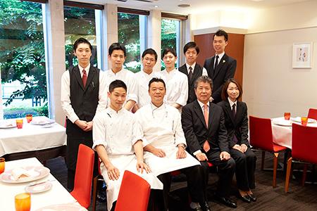 「松本シェフ(前列左から2番目)、オーナーの中村 緻輔悠さん(前列左から3番目)、ほかスタッフの皆さん。どんなシーンでも安心して会食ができる、心地よいサービスが魅力。