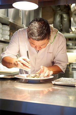 自由な発想という究極のこだわりをひと皿に込めて。真剣な眼差しで料理を仕上げる武田シェフ。思いがけない繊細さを垣間見ることができるシェフの料理は、美しいビジュアルから想像以上の美味しさを約束する。