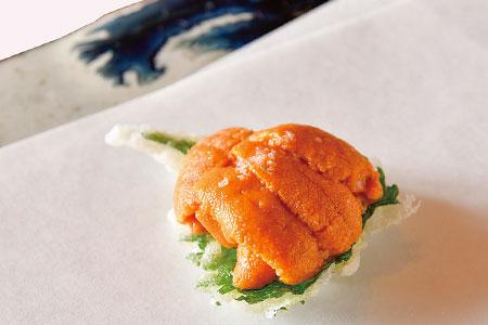 サクサクに揚げた大葉に、黄金色に輝く生うにをたっぷりと乗せた元吉自慢の一品「大葉うにのせ」。能登半島の塩田で作られたお塩でいただく。