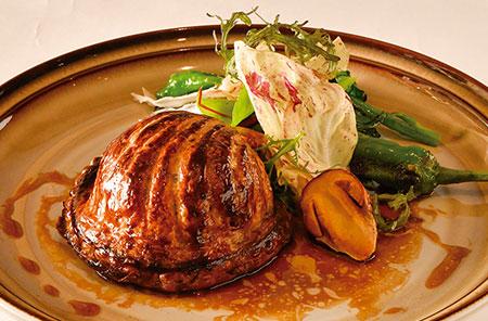 店の看板料理である「パイ包み焼き その日の厳選素材」は、年間を通して旬の食材などを使ったオリジナルの一皿を提供する。写真はバスク地方の郷土料理「アショア(Axoa)」をアレンジした一品。豚肉のミンチを白ワインと万願寺とうがらしで煮込んだフィリングが、素朴ながら味わい深い。