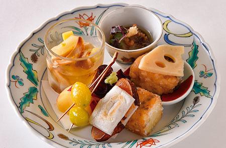 コース料理の先付で提供される一皿。「セロリと焼いたエリンギのお浸し」「なまこ酢」「鰆の南蛮漬け」「帆立のすり身と丹波しめじのしんじょ」「からすみ餅」「たこのやわらか煮」「さつまいものレモン煮」「銀杏の素揚げ」。素材の味を生かしながら丁寧に仕込まれた料理に箸が進む。アラカルトでも注文できる。