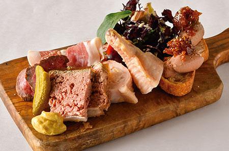 「シャルキュトリーの盛り合わせ」。鶏の白レバーのムース、大山鶏の手羽先(エビとフォアグラをつめたもの)、パテドグランメール(鶏と豚のレバーで作るおばあちゃん風パテ)、宮城赤牛の冷製ローストビーフ、生ハムが楽しめる、同店一番人気メニュー