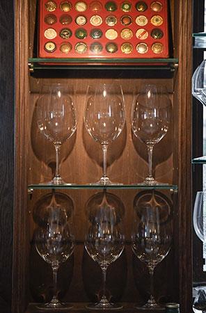 個性豊かなミュズレ(シャンパンのコルク押さえ)が並ぶボードとワイングラス。