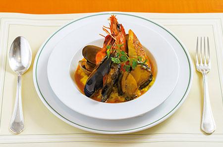 ホテル開業90周年企画『シェフの一皿』で、10月に登場する「シーフードリゾット」。海老や貝などからとったダシを使ったブイヨンで炊き上げたサフランライスは、一口食べれば濃厚な魚介の旨味が広がる。同ホテル伝統のムニエルソースで仕上げるなど、クラシカルな伝統と長谷さんのオリジナリティが融合した一品。