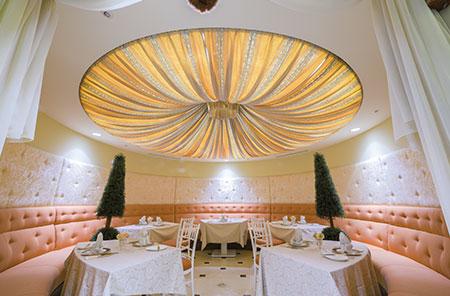 円形の天井に天蓋のようにしつらえたファブリックが印象的。ゆったりと寛げるソファーシートも。