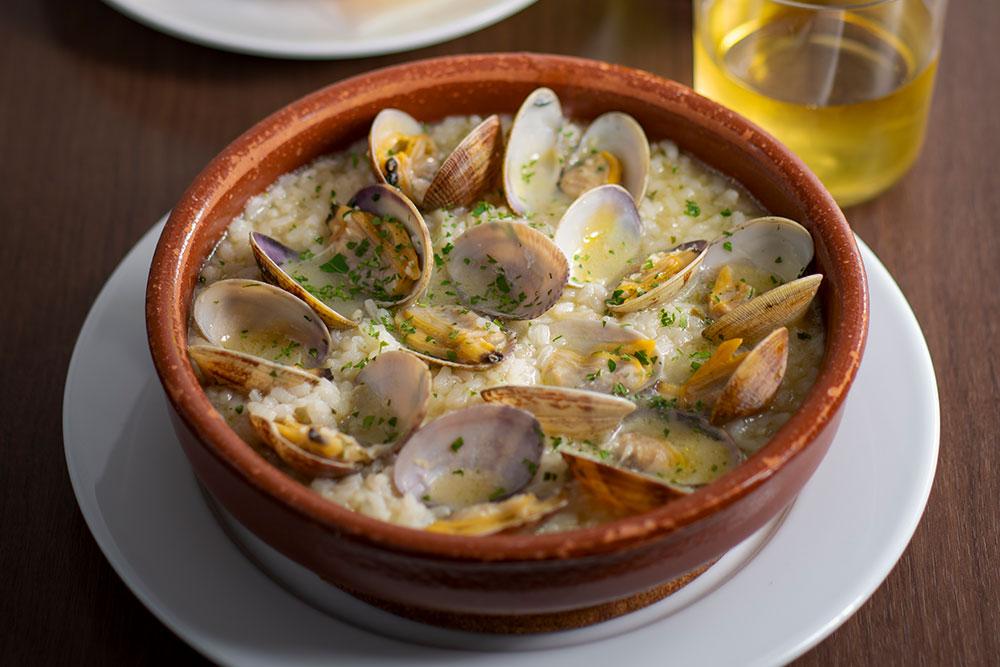 バスク風あさりご飯 バスク地方の代表的な郷土料理。あさりをはじめとした貝のスープで炊き上げた、濃厚な旨みを堪能できる人気の一皿。